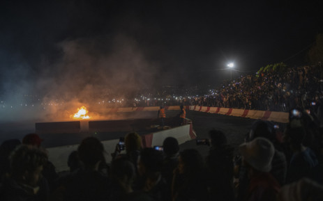 """The car of spinner """"Katra"""" bursts into flames during a stunt at a spinning event in Alberton, on 23 September 2021. Born in the South African townships during the Apartheid era as a ritual to honour fallen gangsters, spinning - stunts performed with heavily modified cars - is now a vibrant motorsport with a large underground following. Picture: Michele Spatari/AFP"""