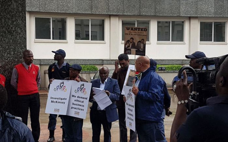 Demonstrators hold up posters during a protest against McKinsey over 'irregular payments' involving Eskom and Trillian on 5 October 2017. Picture: Supplied.