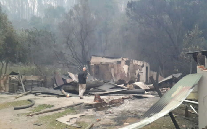 A resident rummages through what's left of a house gutted by the Knysna fire. Picture: EWN.