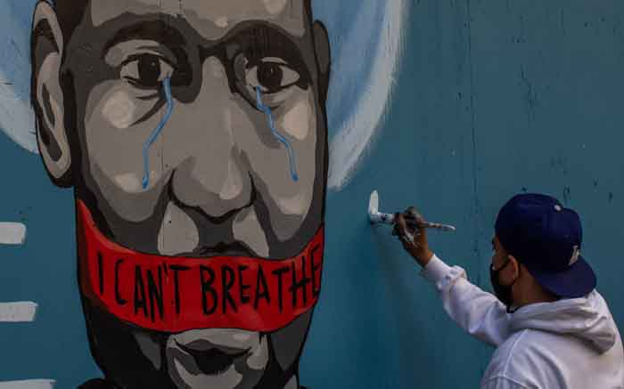 The artist Celos paints a mural in downtown Los Angeles on 30 May 2020 in protest against the death of George Floyd, an unarmed black man who died while while being arrested and pinned to the ground by the knee of a Minneapolis police officer. Picture: AFP