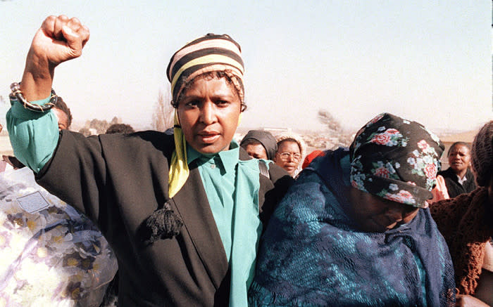 """FILE: Winnie Madikizela-Mandela (l), raises a clenched fist on 27 July 1987 during the funeral of Sello Motau, senior member of the """"Umkhonto We Sizwe"""", the ANC military wing, who was gunned down in Swaziland 9 July 1987. Picture: AFP"""