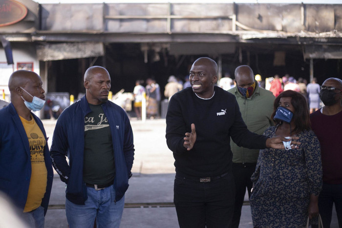 Residents listen as Thandanani Mabanga, an independent ward councillor for Inanda, speaks about the way forward after the violent unrest in the area on 20 July.