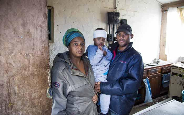 Jermain, his wife Gracia, and their son Joden in their home where the roof was ripped off during the night, injuring their son on his head. He was taken to hospital and treated for gashes. Picture: Thomas Holder/ EWN.