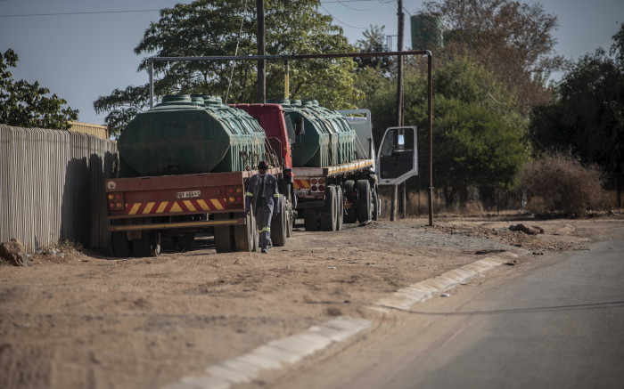 Lucas Tebeila, resident of Apel, passes a water tank being filled by the pumps of Fetakgomo Tubatse municipality. Picture: Abigail Javier/EWN