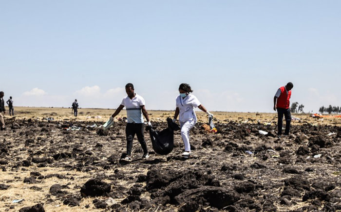 Rescue team members carry bodies in bags at the crash site of an Ethiopian Airlines Boeing 737 MAX near Bishoftu, some 60 kilometres southeast of Addis Ababa, Ethiopia, on 10 March 2019. Picture: AFP