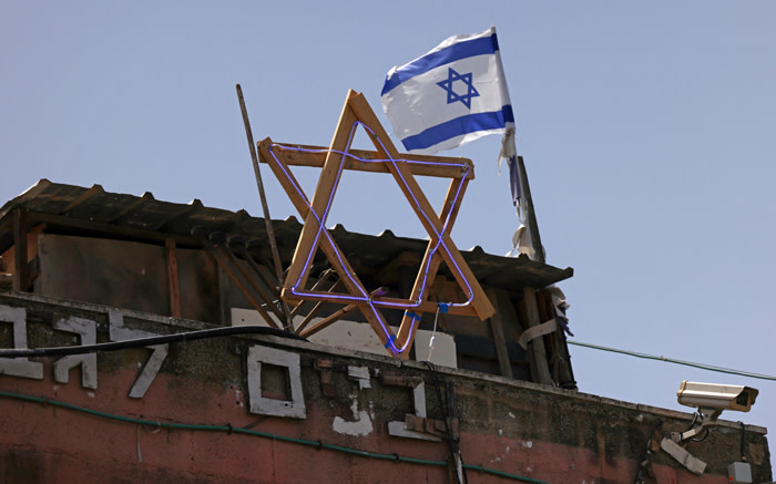 The Star of David and an Israeli flag are seen on top of a house in the Sheikh Jarrah neighbourhood of occupied east Jerusalem on 5 May 2021. Israeli Jews backed by courts have taken over houses in Sheikh Jarrah in east Jerusalem on the grounds that Jewish families lived there before fleeing in Israel's 1948 war for independence. Picture: Emmanuel DUNAND/AFP
