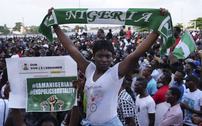 A protester holds up a scarf with the same colours as the Nigerian national flag during a live concert at the Lekki toll gate in Lagos, Nigeria, on 15 October 2020, during a demonstration to protest against police brutality and scrapping of Special Anti-Robbery Squad (SARS). Picture: AFP.