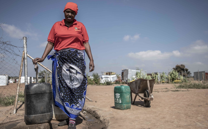 Tebogo Mantsena, a resident of Juju Valley, filling her containers with water. Juju Valley lacks basic services such as running taps. Picture: Abigail Javier/EWN