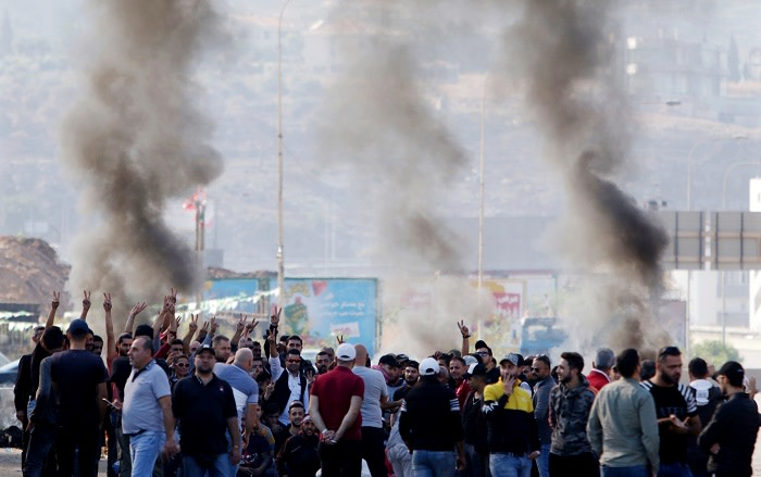 Lebanese protesters gather next to burning tyres to block the southern entrance of the capital of north Lebanon Tripoli, as anti-government demonstrations continued on 12 November 2019 across the country. Picture: AFP