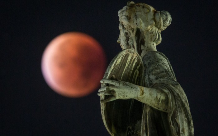 16f378d735f0 The supermoon or blood moon seen behind a statue during a total lunar  eclipse in Frankfurt