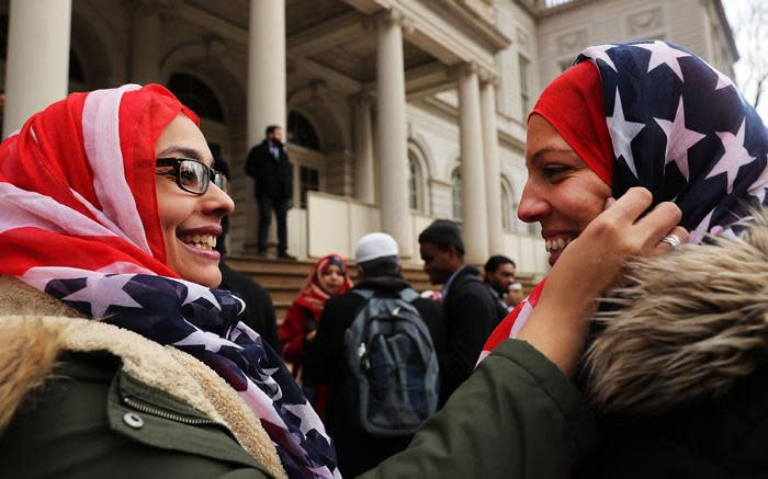 New York City police officers Aml Elsokary and Maritza Morales wear American flag headscarves at an event at City Hall for World Hijab Day on 1 February 2017 in New York City. Picture: AFP.