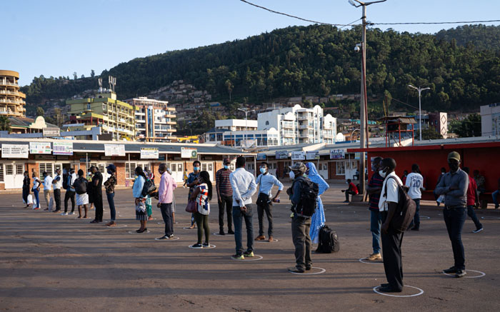 People stand in white circles drawn on the ground to adhere to social distancing measures to curb the spread of COVID-19 as they wait for a bus at Nyabugogo bus station in Kigali, Rwanda, on 4 May 2020, the first day back from the nationwide coronavirus lockdown. Picture: AFP