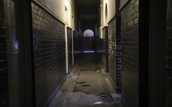 A corridor between the flats of the old Johannesburg central fire station with broken wooden floor tiles. Picture: Abigail Javier/EWN