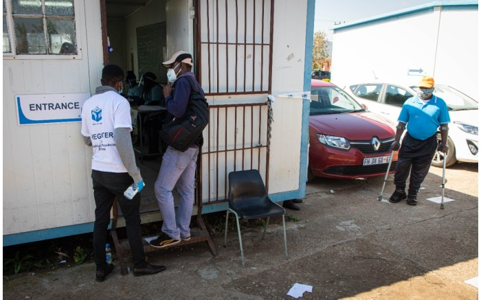 Voters being socially distanced and sanitised before entering a voting station in Ward 30, at Rantailane Secondary School in Ga-Rankuwa.