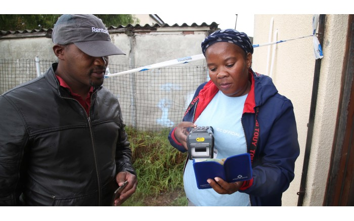 An IEC Election official scans a residents barcoded I.D allowing them to start their voting process. Picture: Bertram Malgas