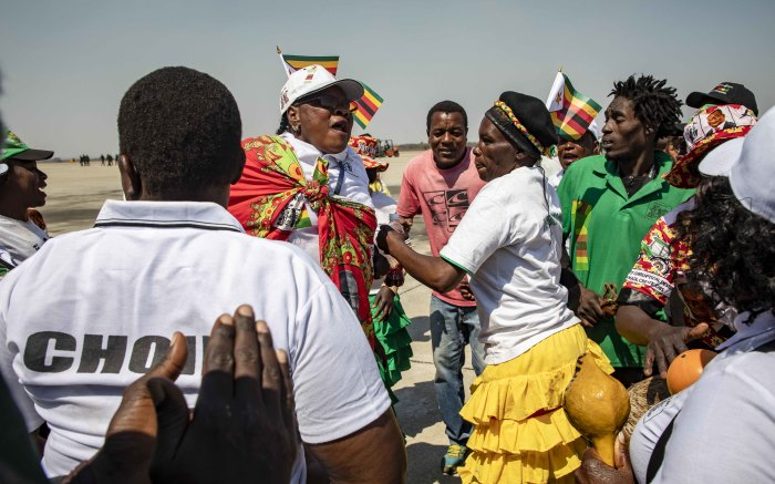 Choirs sing and dance as they wait for Robert Mugabe's body to arrive at his namesake airport.
