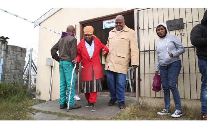 An elderly woman is help after voting at the Red Cross Society voting station. Picture: Bertram Malgas