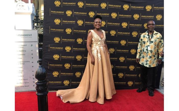 Public Protector Busisiwe Mkhwebane in a flowing gold gown.