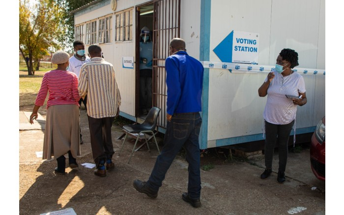 A voting station presiding officer supervises voters as they arrive to vote in the by-elections in Ward 30.