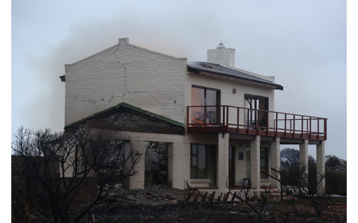 A house in the Overstrand region of the Western Cape smoulders after it caught fire during a wildfire on 11 January 2019. Picture: EWN