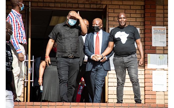 EFF leader Julius Malema (in red tie) outside the court.