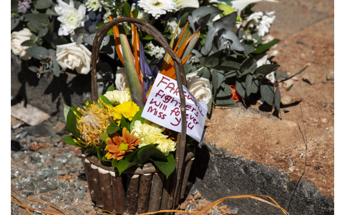 A message on some of the flowers placed at the site for the fallen firefighter.