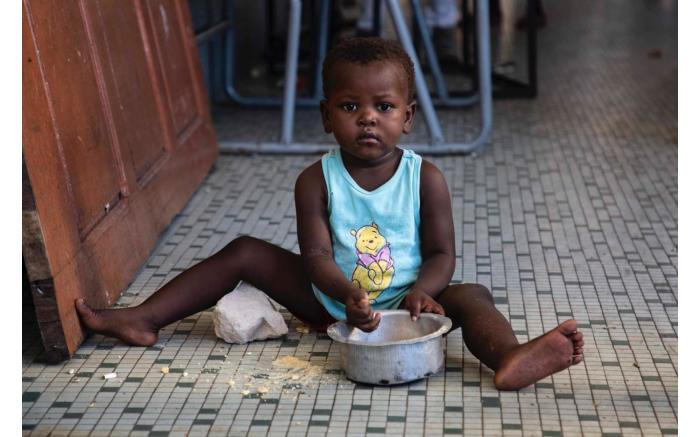 A child eats lunch in a shelter set up for victims of Cyclone Idai. Christa Eybers/EWN