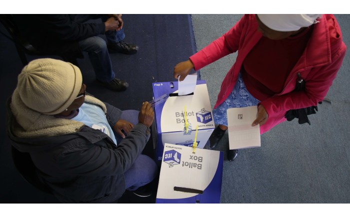 A voter is seen placing her marked ballots into the local and National ballot boxes. Picture: Bertram Malgas