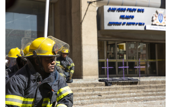 A firefighter sits in front of the Bank of Lisbon building where 3 of his colleagues died while trying to extinguish a fire.