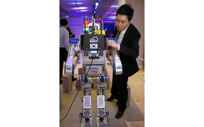 A delegate inspects a robot at the World Economic Forum's annual meeting in Davos. Picture: swiss-image.ch