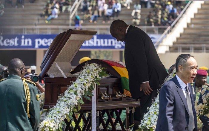 SA President Cyril Ramaphosa bows his head to the late former President Robert Mugabe.