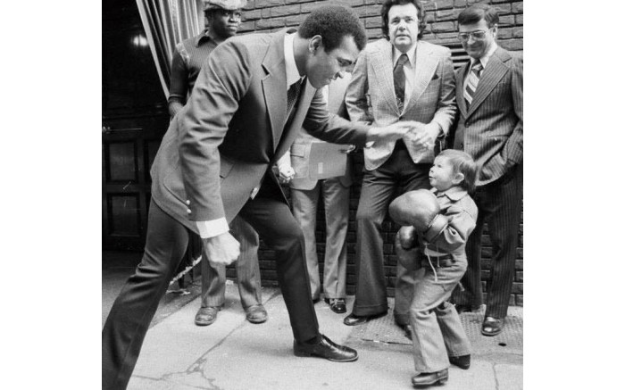 Muhammad Ali takes a picture with a little boy while on tour.