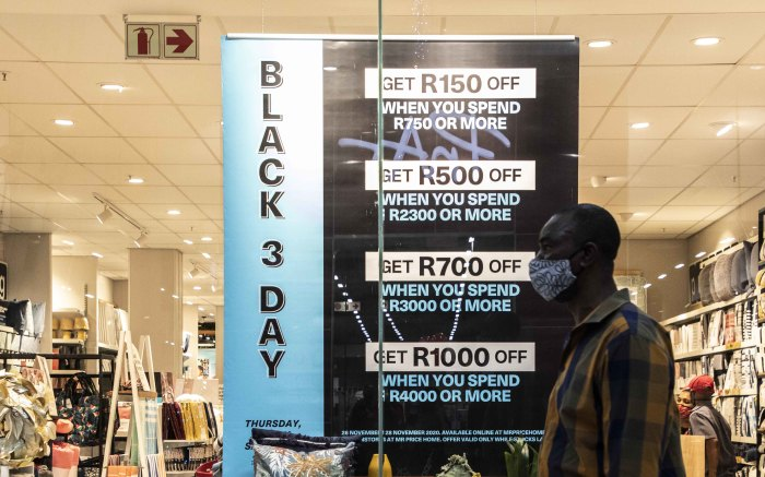 Man walks past a Black Friday store special in Greenstone shopping centre.