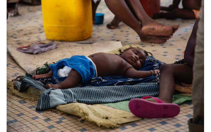A baby sleeps on the floor in a shelter set up for people displaced by Cyclone Idai. Christa Eybers/EWN