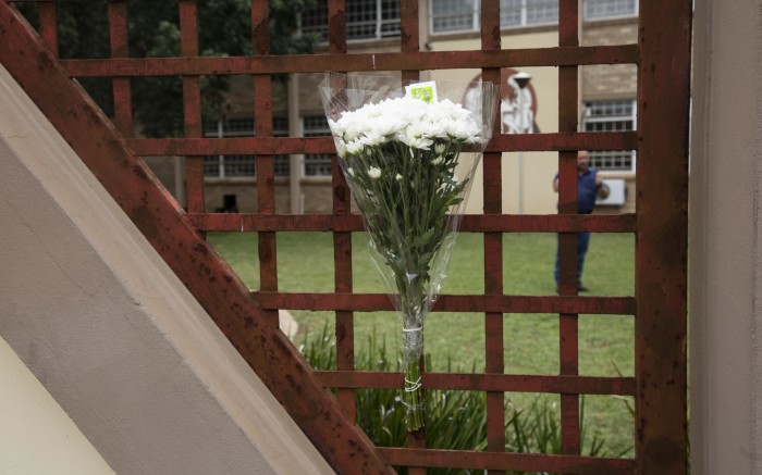 Flowers on the gate outside Hoërskool Driehoek where a structural collapse killed 4 children.