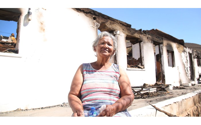 71-year-old Nolene Salomo sits in front of her neighbour's burnt out house in Wupperthal. Pictures: Bertram Malgas/EWN