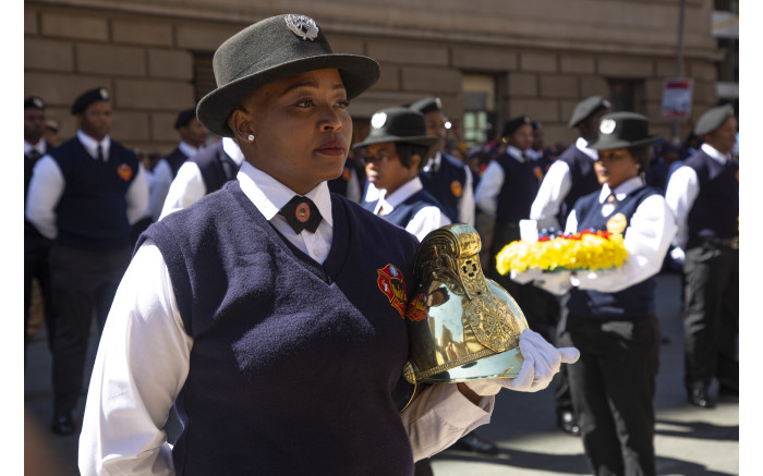 A member of the Johannesburg EMS stands with a golden helmet as they honour their colleagues.