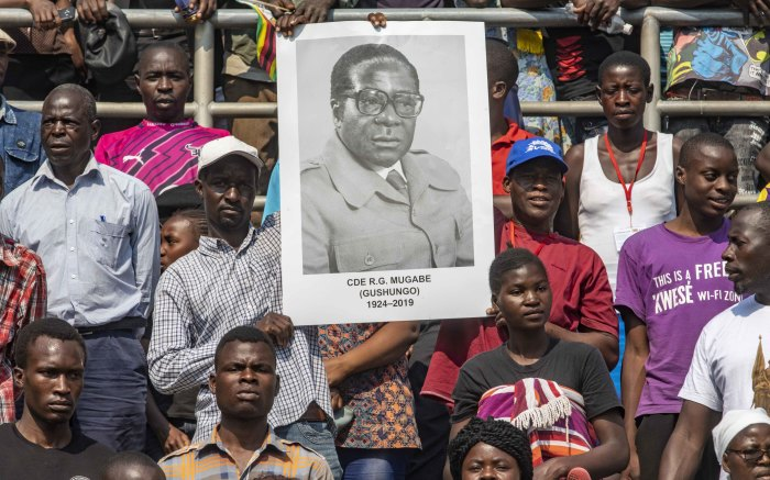 Supporters of former President Robert Mugabe hold a poster up of their leader in the National Sports Stadium.