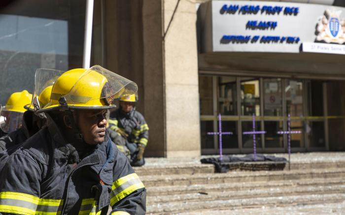 Firefighters sit in front of the Bank of Lisbon building in 2018, paying tribute to those fallen.  Picture: Christa Eybers/EWN