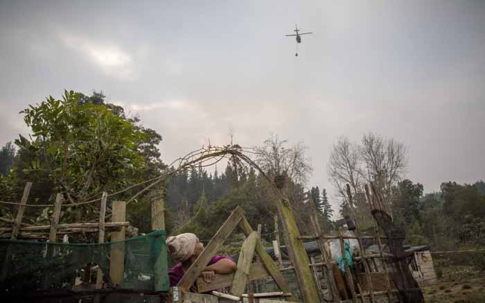 A resident of Concordia, an informal settlement in Knysna, looks overhead at a water bombing helicopter. Picture: Thomas Holder/EWN.