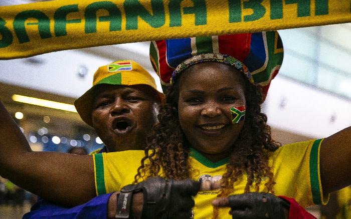 A Bafana Bafana supporter carries a Bafana Bafana scarf while waiting at OR Tambo International Airport. Picture: Kayleen Morgan/EWN