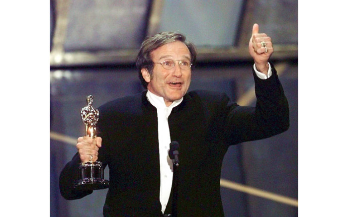 """Actor Robin Williams holds up his Oscar after winning in the Best Actor in a Supporting Role category during the 70th Academy Awards 23 March at the Shrine Auditorium in Los Angeles. Williams won for his role as a psychotherapist helping a troubled math genius in """"Good Will Hunting."""" Picture: AFP."""