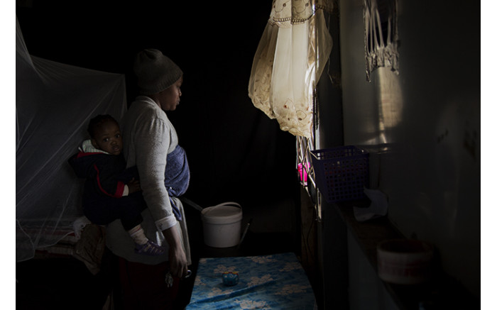 A woman looks through her window after heavy rains flooded her home in an informal settlement in Soshanguve, Pretoria. Picture: Sethembiso Z