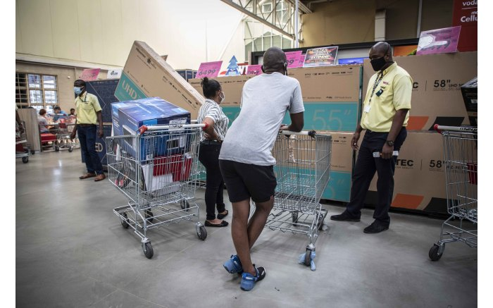 Shoppers speaking to a Makro Woodmead salesman about the latest Black Friday television deals.