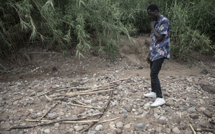 Enock Mpianzi's older brother Yves Kadilo inspects material he believes was used to make make-shift rafts.