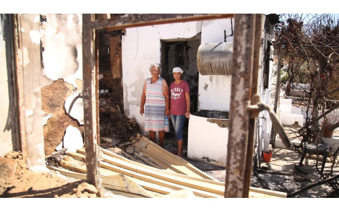 71-year-old Nolene Salomo walks through what is left of her home after it burnt down. Pictures: Bertram Malgas/EWN
