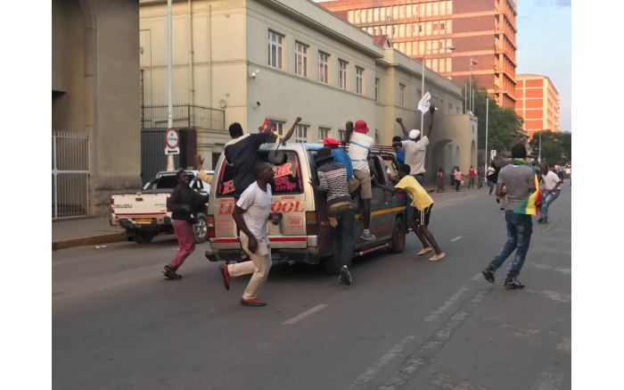 Crowds of people in Harare rush to dance near the army tanks to celebrate as Robert Mugabe resigned. Picture: Ihsaan Haffajee/EWN.
