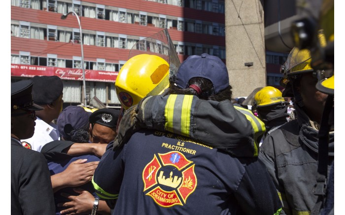 Firefighters who fought the blaze with those who died comfort each other as they remember their colleagues.