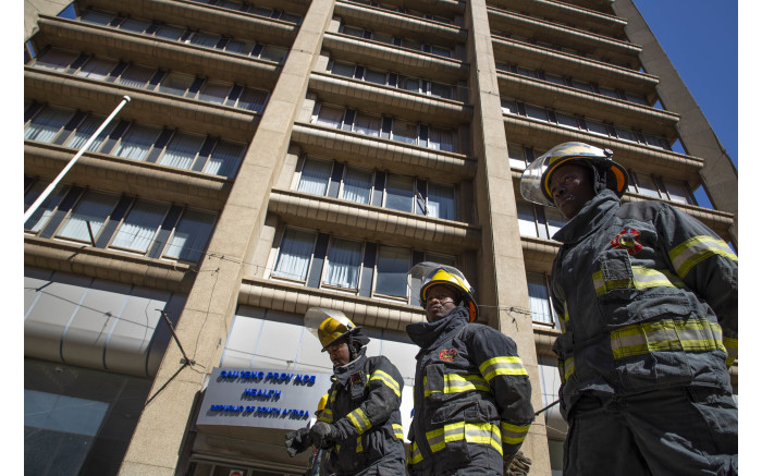 Firefighters stand in front of the Bank of Lisbon building where 3 of their colleagues died while trying to extinguish a fire.