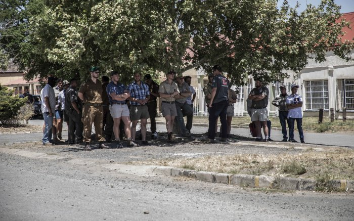 Farmers watch across the road where the EFF members are protesting outside outside Senekal Magistrates court. Picture: Abigail Javier/EWN